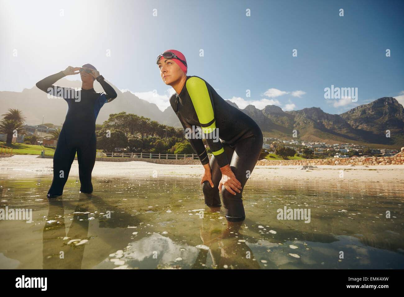 Determined sports persons standing in water getting ready for competition. Triathletes in wet suits preparing for - Stock Image