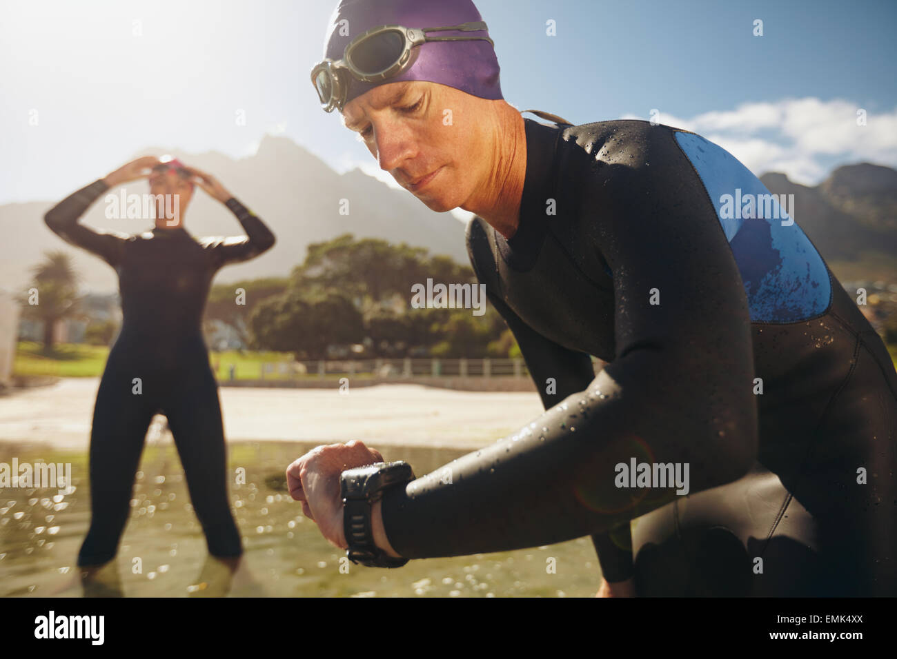 Focused young man checking his watch while in wetsuit at the lake. Man looking at watch after practice run. Triathletes. - Stock Image