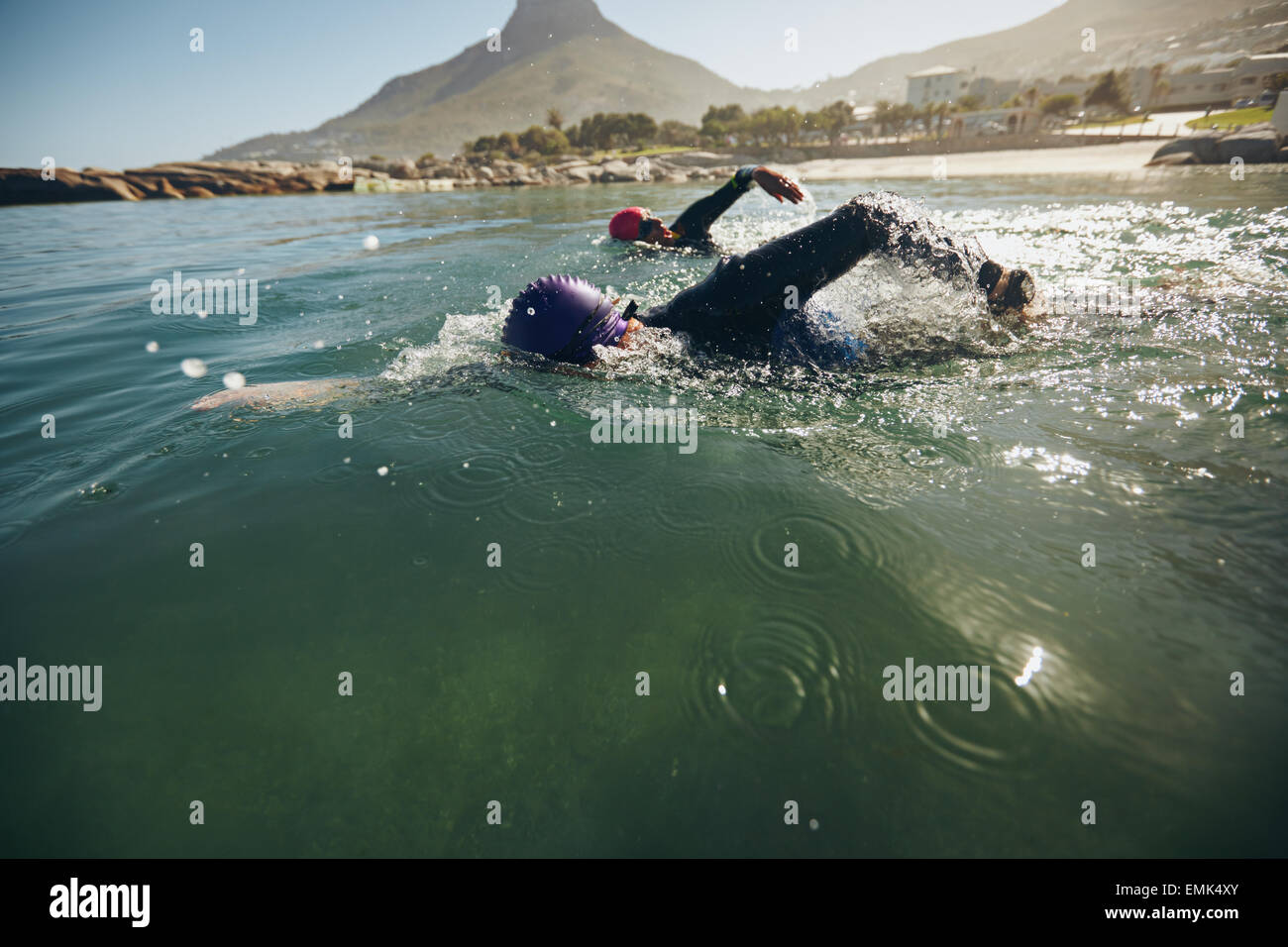 Triathlon swimmers churning up the water. Athletes practicing for triathletic race in lake. - Stock Image