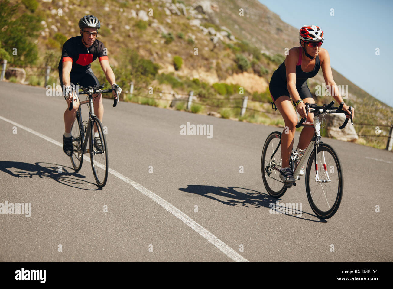 Woman competing in the cycling leg of a triathlon with male competitor. Triathletes riding bicycle on open road. - Stock Image