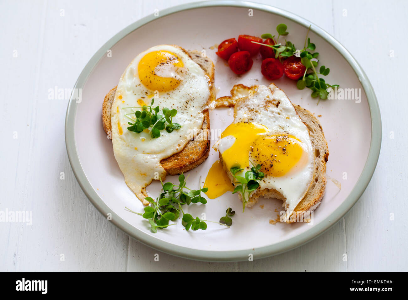 Breakfast, eggs on toast with cherry tomatoes and cress Stock Photo