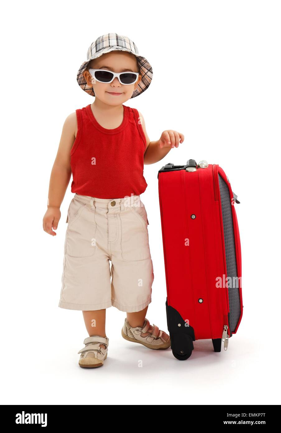 Little boy in sunglasses and hat, standing near luggage, ready for summer vacation - Stock Image