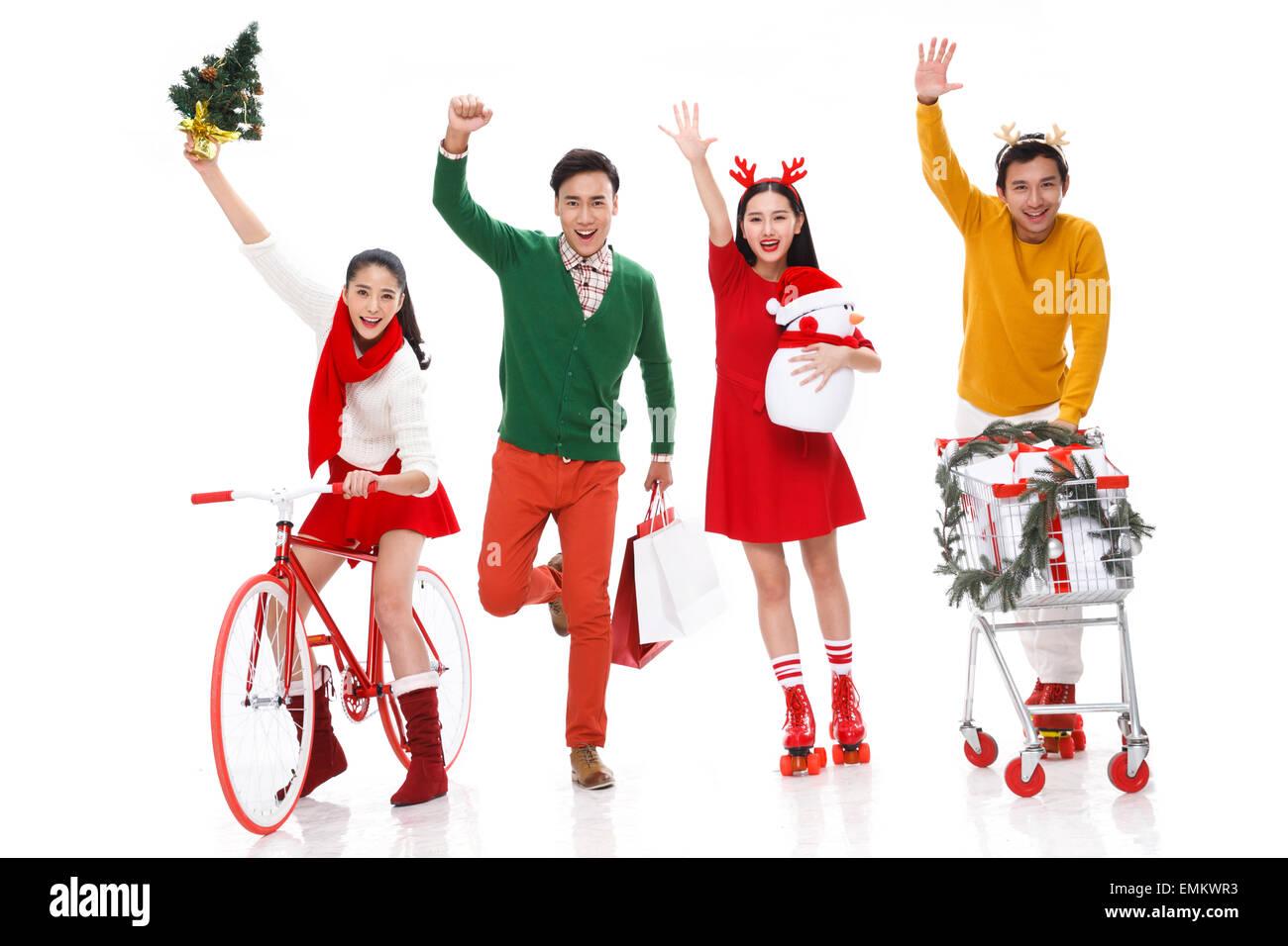 Young men and women joyous Christmas shopping - Stock Image