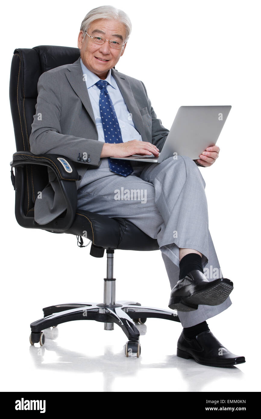 An elderly man was sitting in the boss chair to use a computer - Stock Image
