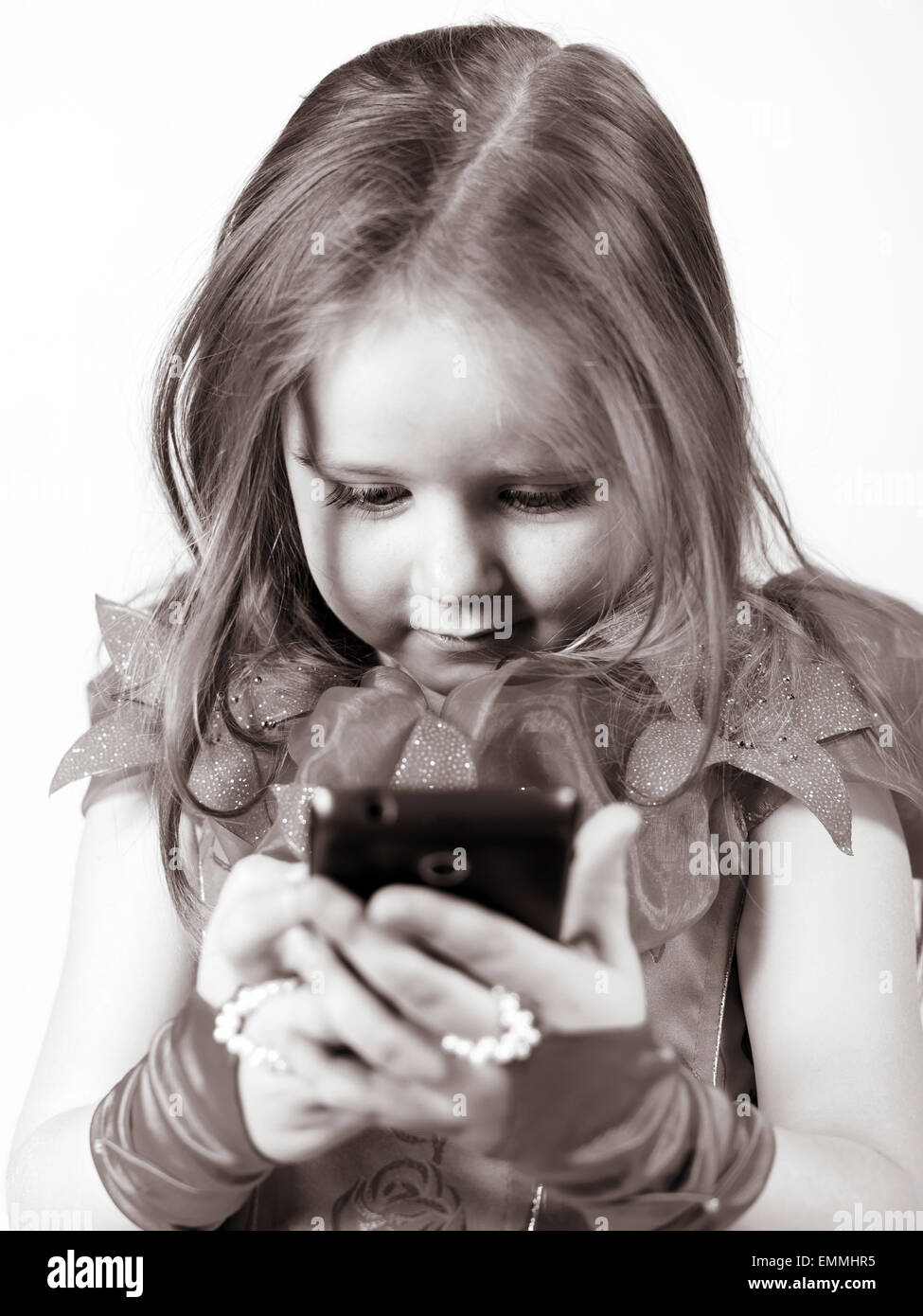 Cute little girl dressed in ball gown playing with smartphone and smiling, isolated on white background Stock Photo