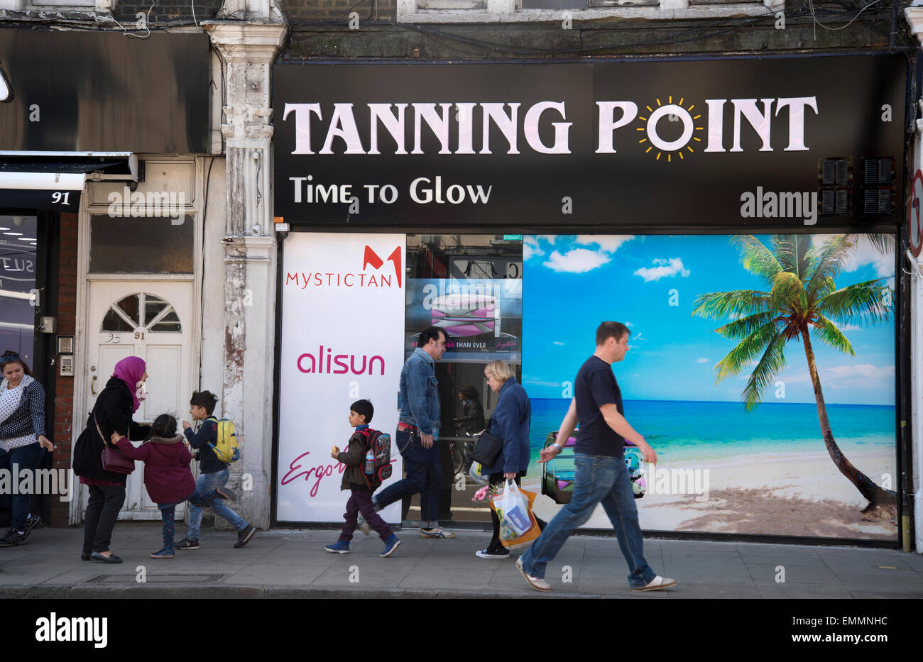 Hackney, London. Stoke Newington High Street. Tanning studio with palm tree photo and people walking past on the - Stock Image