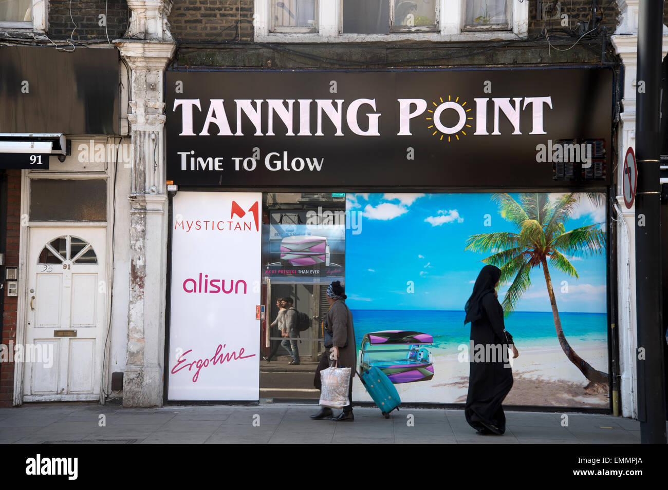 Tanning studio with palm tree beach photo mural and people walking past on the pavement including woman in Islamic - Stock Image