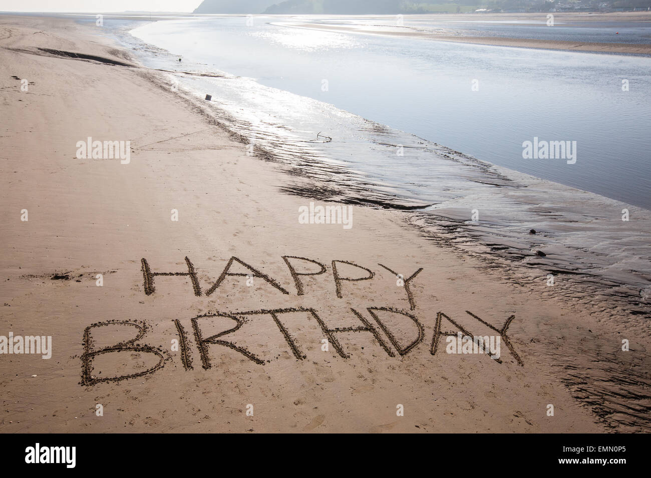 'Happy Birthday' written in the sands on the beach at Ferryside with Llanstephan in the background,Carmarthenshire,West - Stock Image