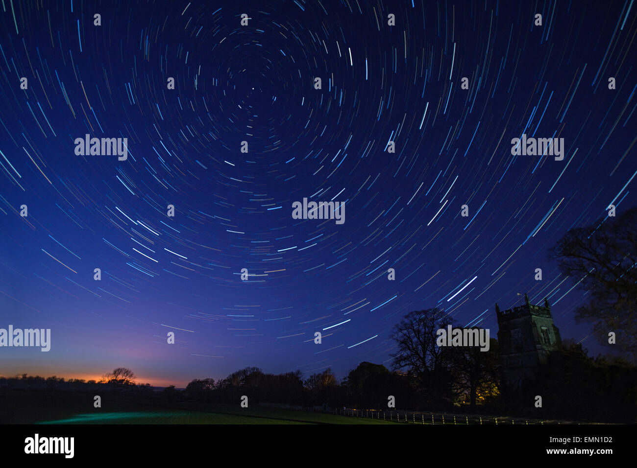 Astronomy - Star Trails in early Spring above a village church in a small village in North Yorkshire in the United - Stock Image