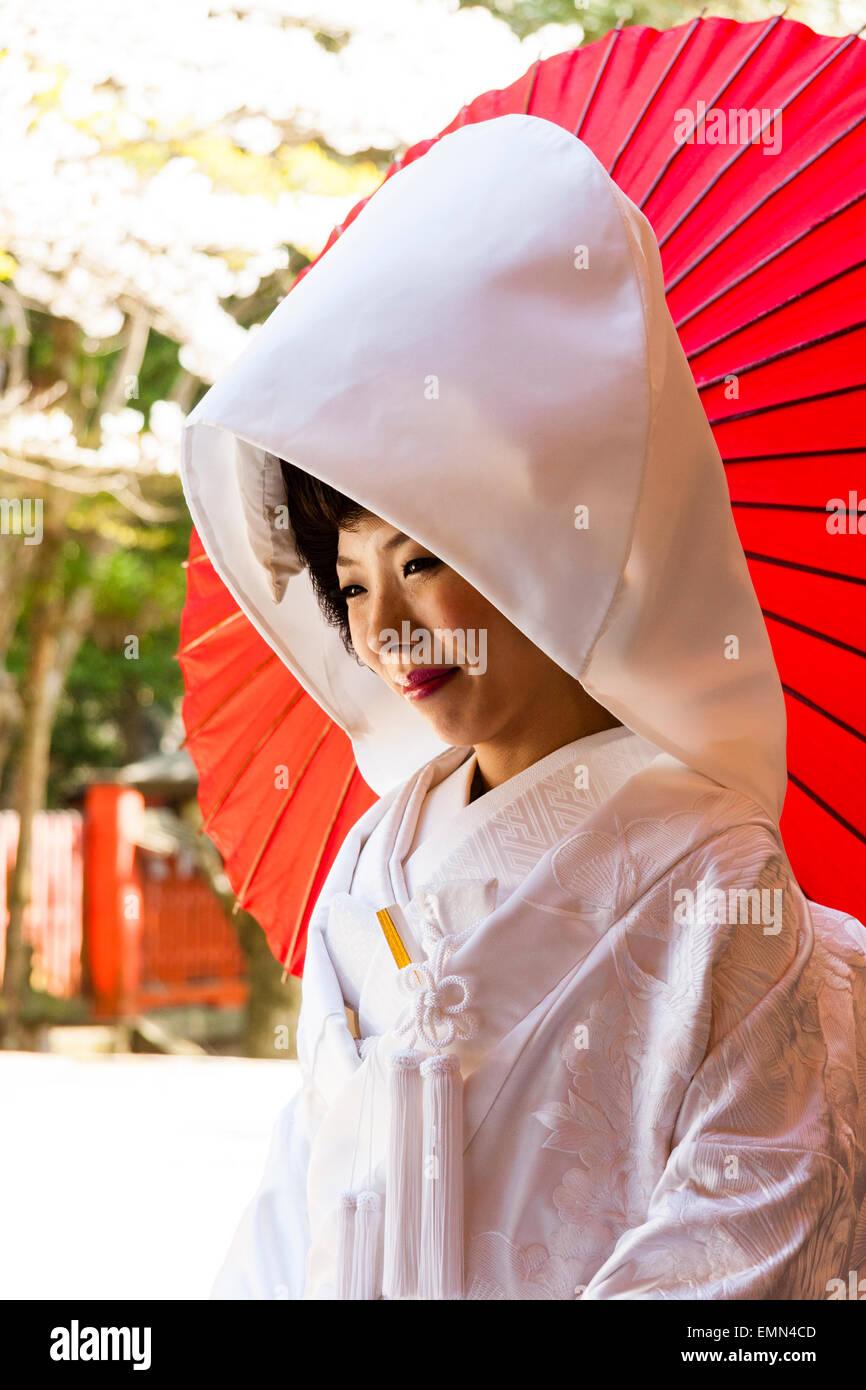 Japan, Nara, Tamukeyama shrine. Japanese bride sitting in traditional shiromuku white kimono, smiling with red parasol, paper umbrella behind her. Stock Photo