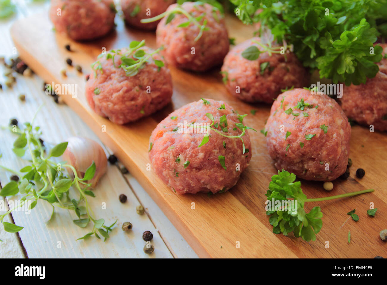 Raw meat balls with fresh parsley and herbs - Stock Image