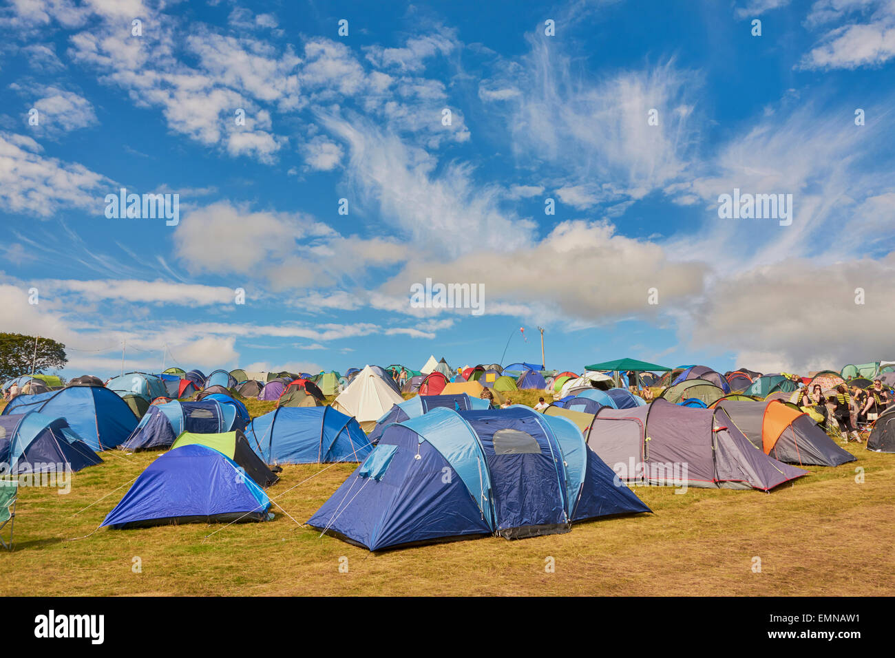 Camping site at Festival No.6, in Portmeirion, Wales, showing different coloured tents against a blue sky with fluffy - Stock Image