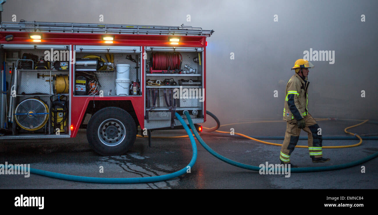 Firemen at the scene of a fire involving a small business. Kopavogur, Iceland - Stock Image