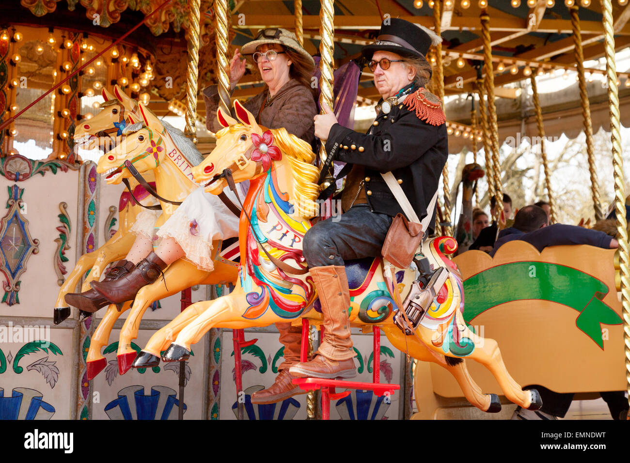 Middle aged caucasian couple having fun on a roundabout or carousel, Norfolk, UK - Stock Image