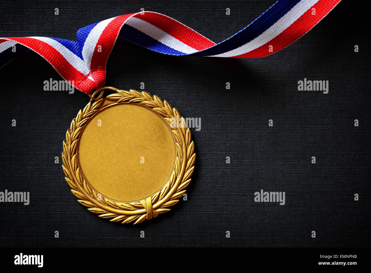 Gold medal on black with blank face for text, concept for winning or success - Stock Image