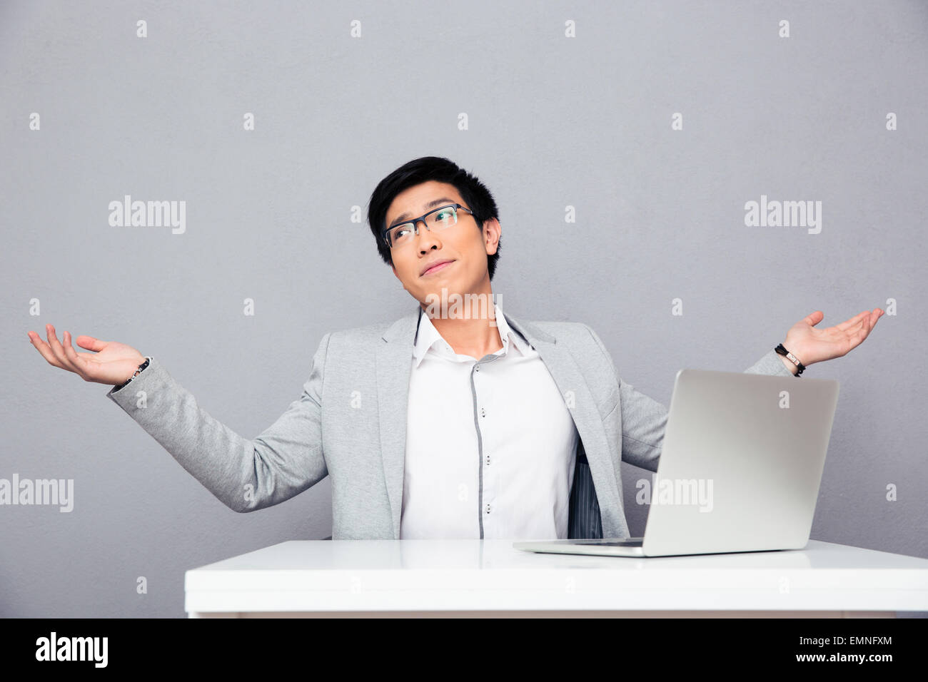 Businessman sitting at the table with laptop and shrugging over gray background - Stock Image