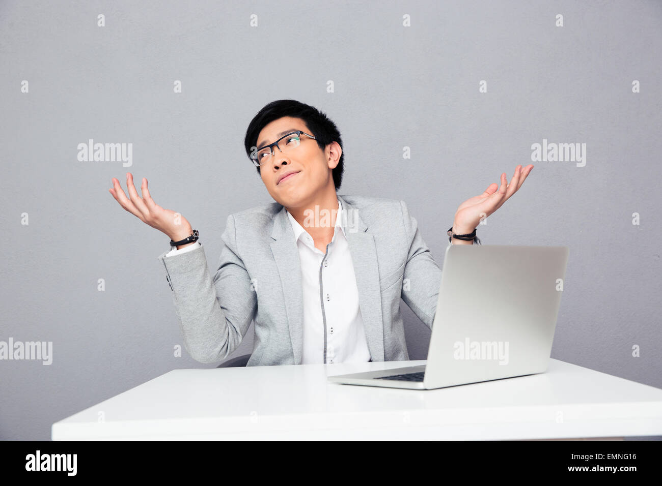 Young businessman sitting at the table with laptop and shrugging over gray background. I dont know. - Stock Image