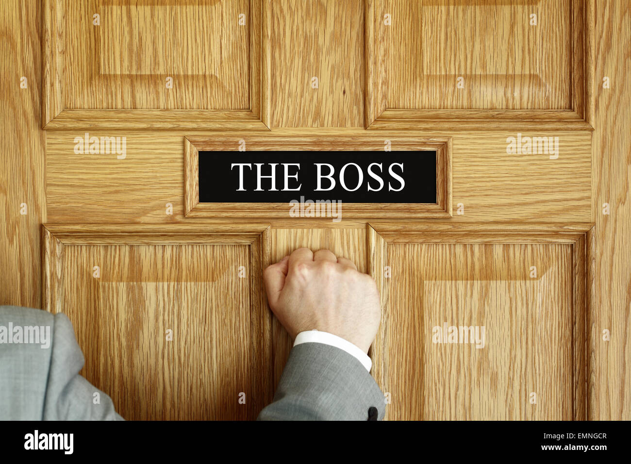 Businessman knocking on a door to 'The Boss' office concept for meeting, trouble, problems, promotion or - Stock Image