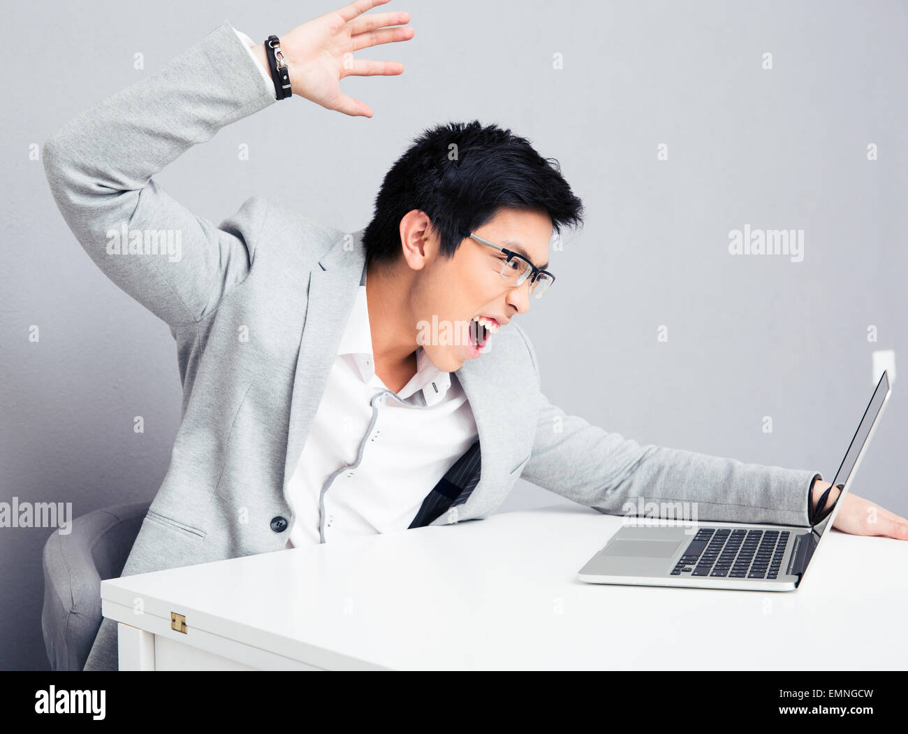 Angry young businessman in glasses sitting at the table with laptop over gray background Stock Photo