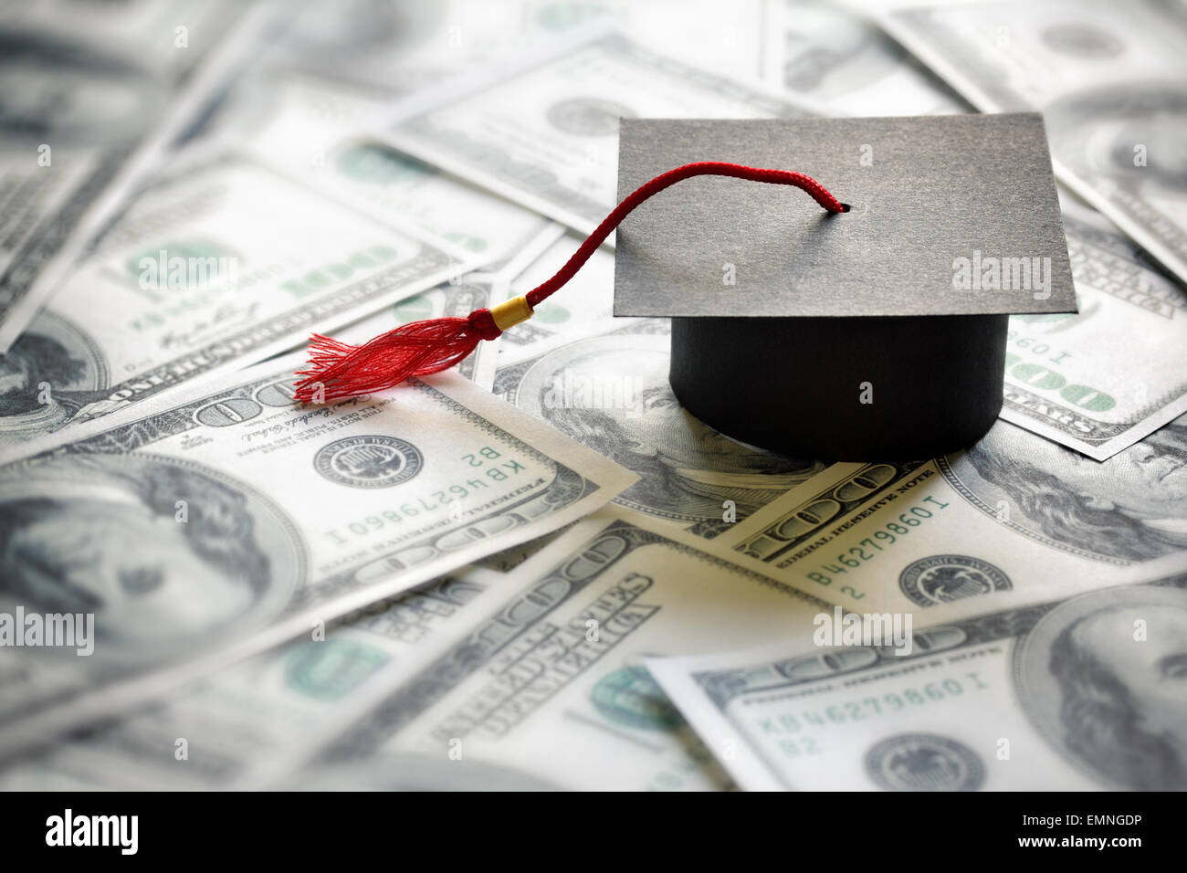 Graduation mortar board cap on one hundred dollar bills concept for the cost of a college and university education - Stock Image