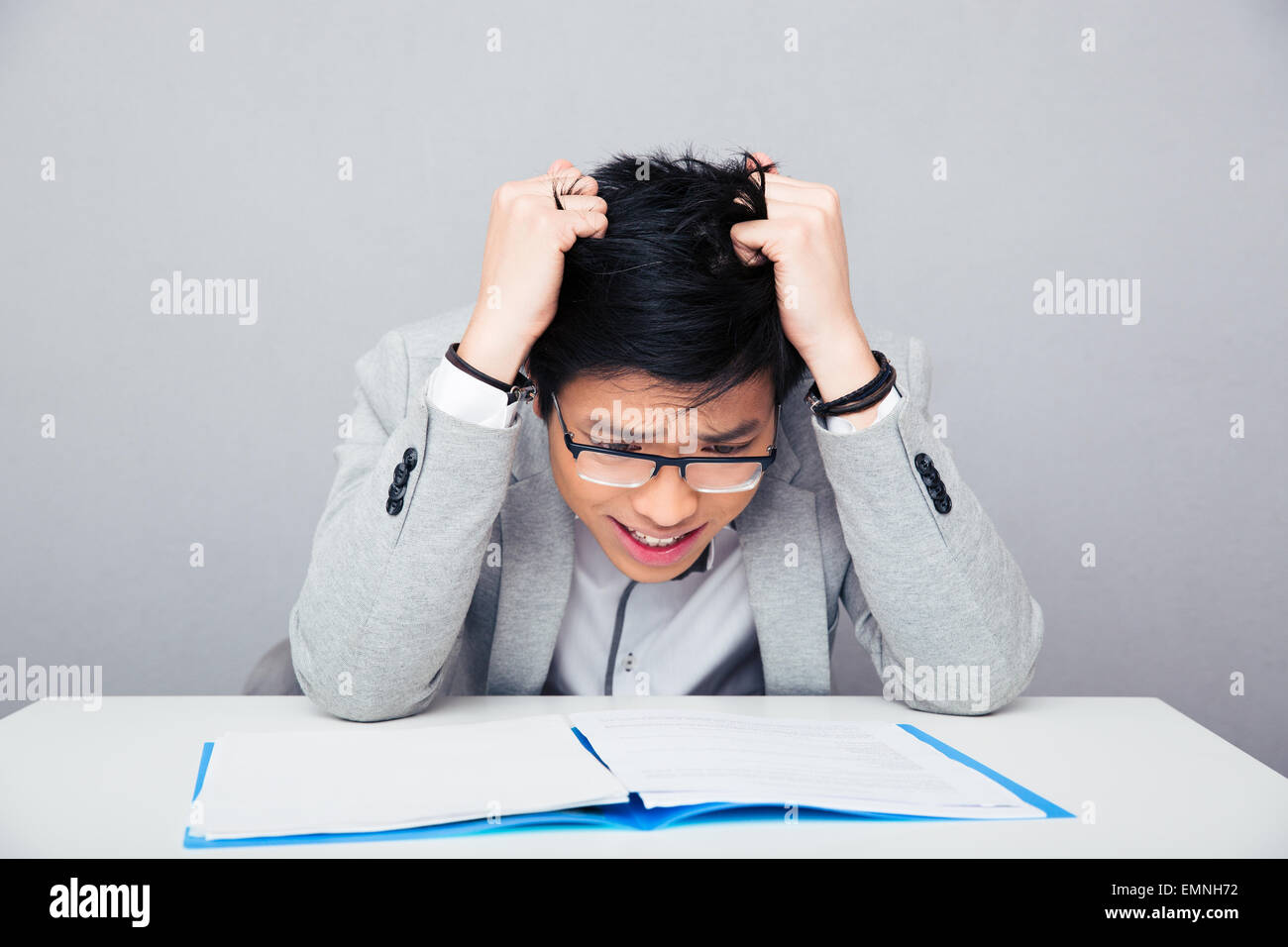 Worried businessman sitting at the table and reading papers over gray background - Stock Image