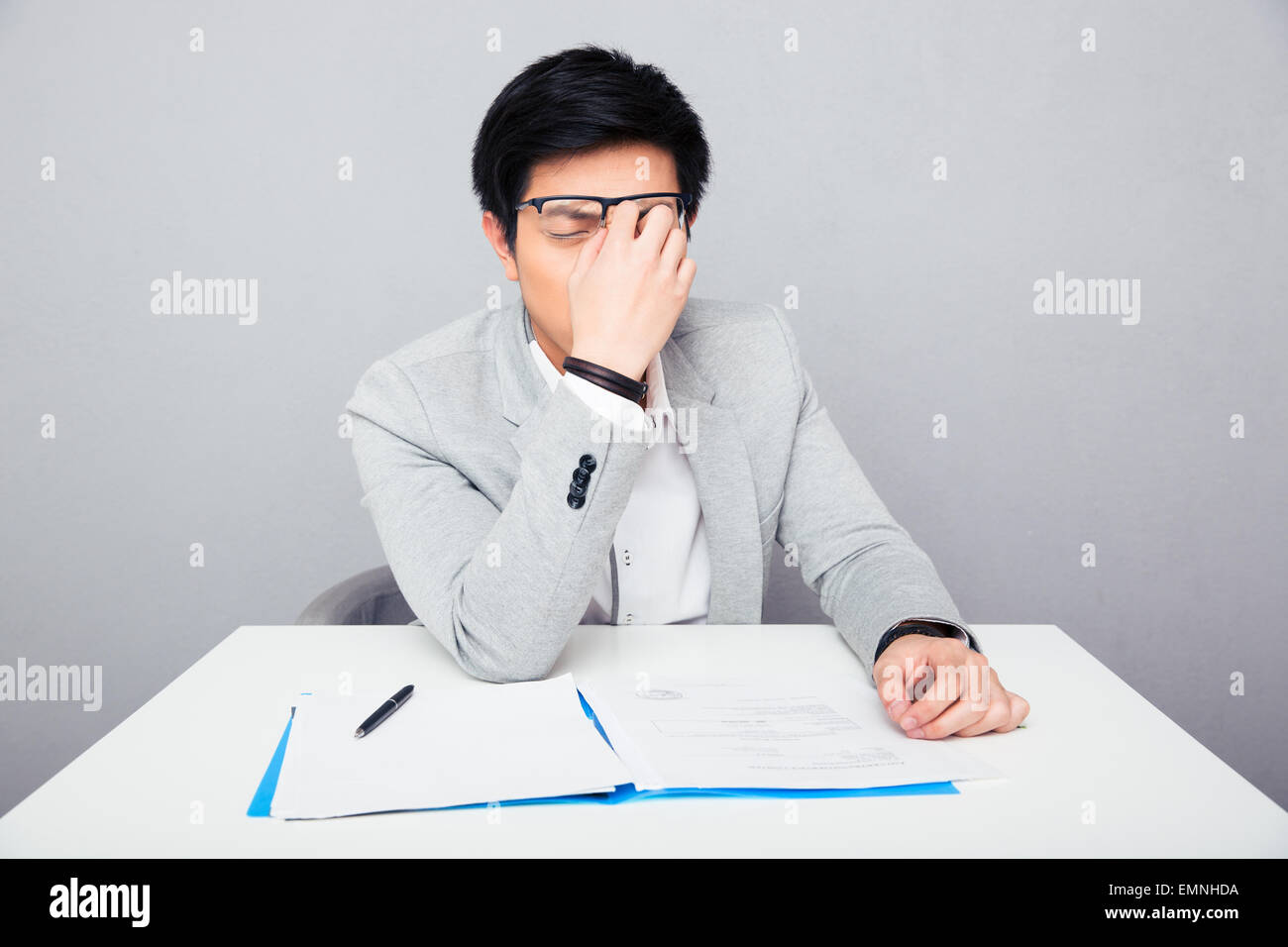 Tired businessman sitting at the table and rubs his nose in office - Stock Image