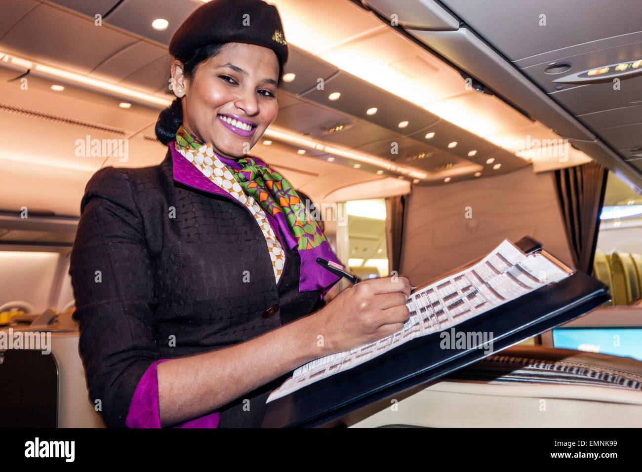 Virginia Dulles International Airport IAD terminal Etihad Airways Business Class onboard cabin Asian woman flight - Stock Image