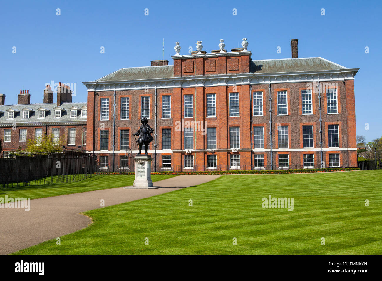 A view of the magnificent Kensington Palace in London with the statue of King William III in the foreground. - Stock Image