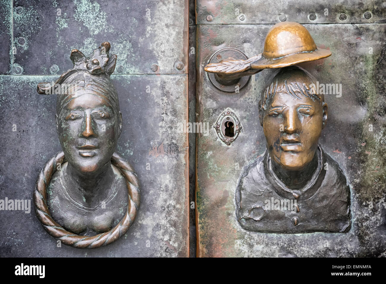 Door made of bronze with the head of a woman and a man as a door knob in Magdeburg, Germany - Stock Image
