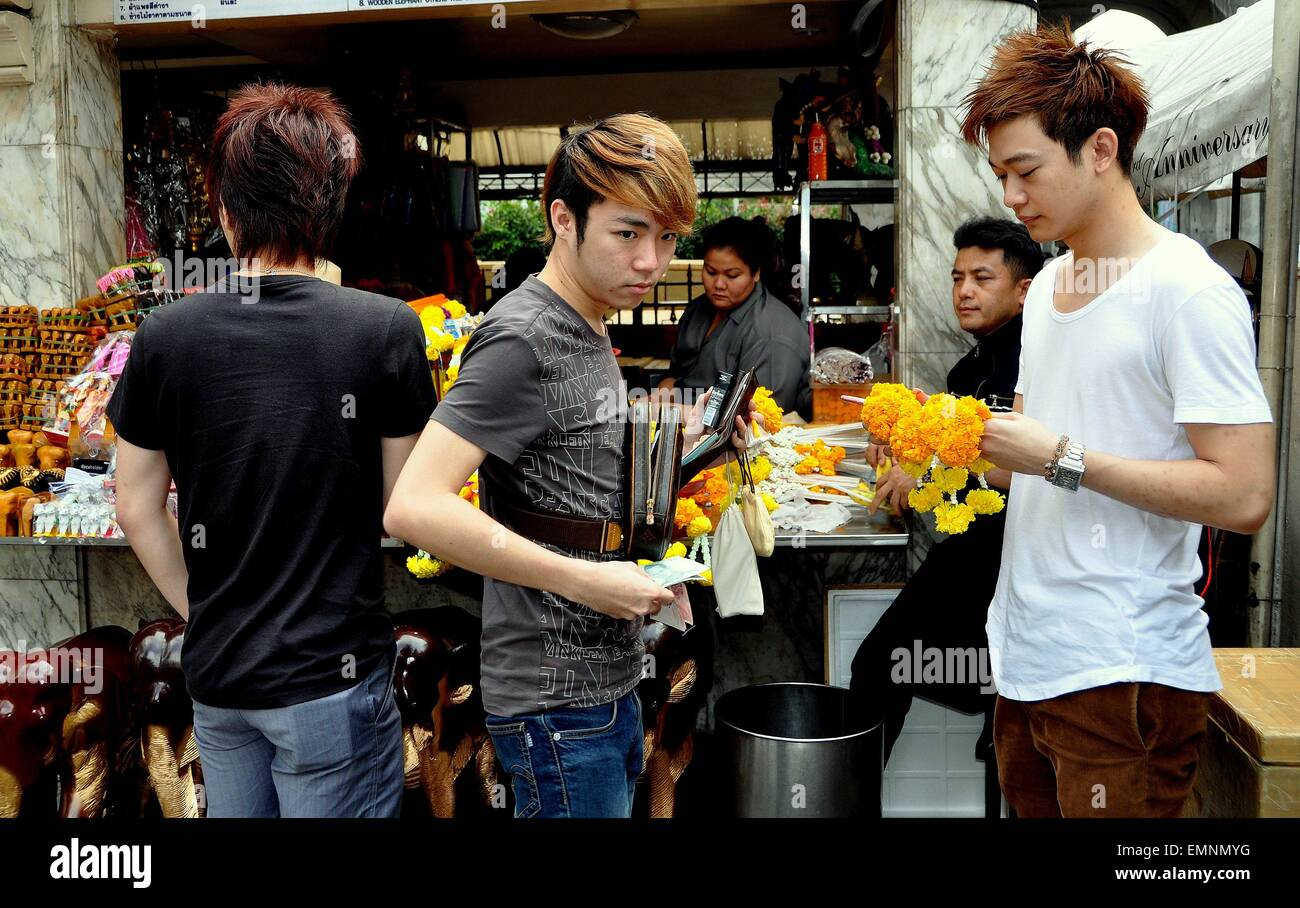 Bangkok, Thailand:  Three Thai youths buying floral tributes from a vendor at the revered Erawan Shrine - Stock Image