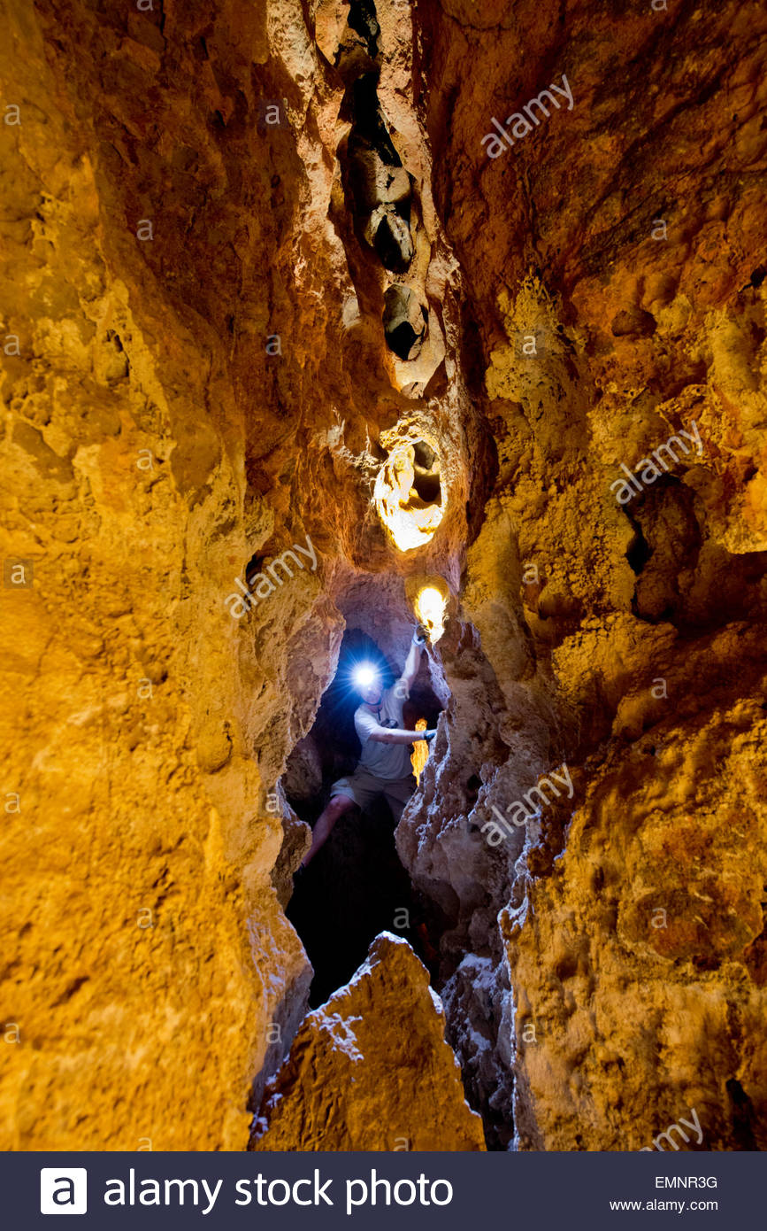 Tour guides helmet light beaming through darkness navigates underneath the Pearl formation Colossal Cave,Tucson, - Stock Image