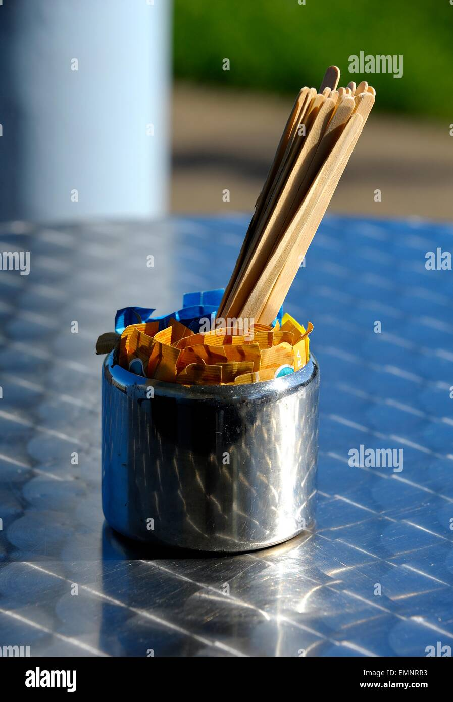 A chrome container with sugars and stirring sticks. - Stock Image