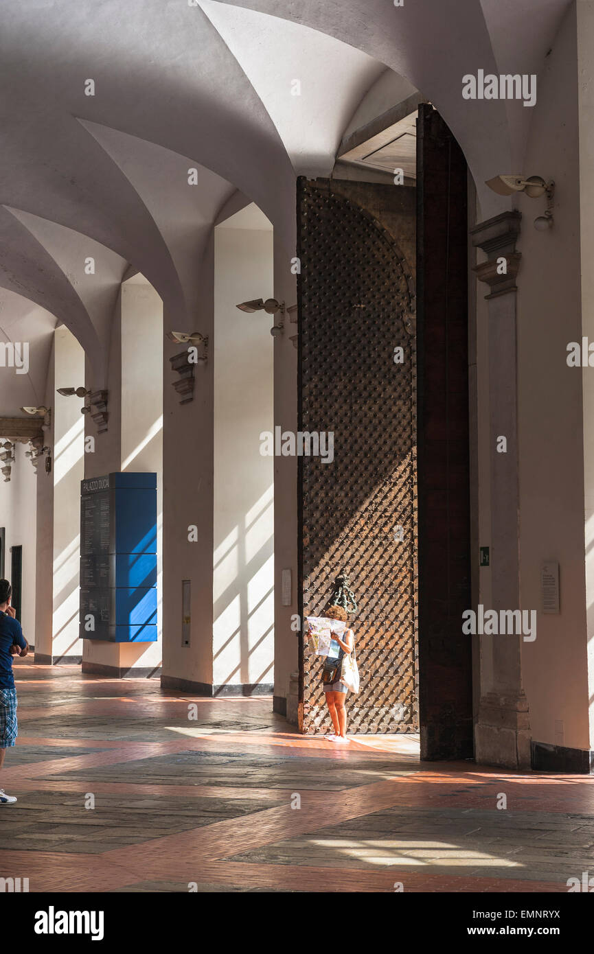 Genoa museum, a woman reads a map inside the vaulted atrium of the Palazzo Ducale, Genoa, Italy. - Stock Image