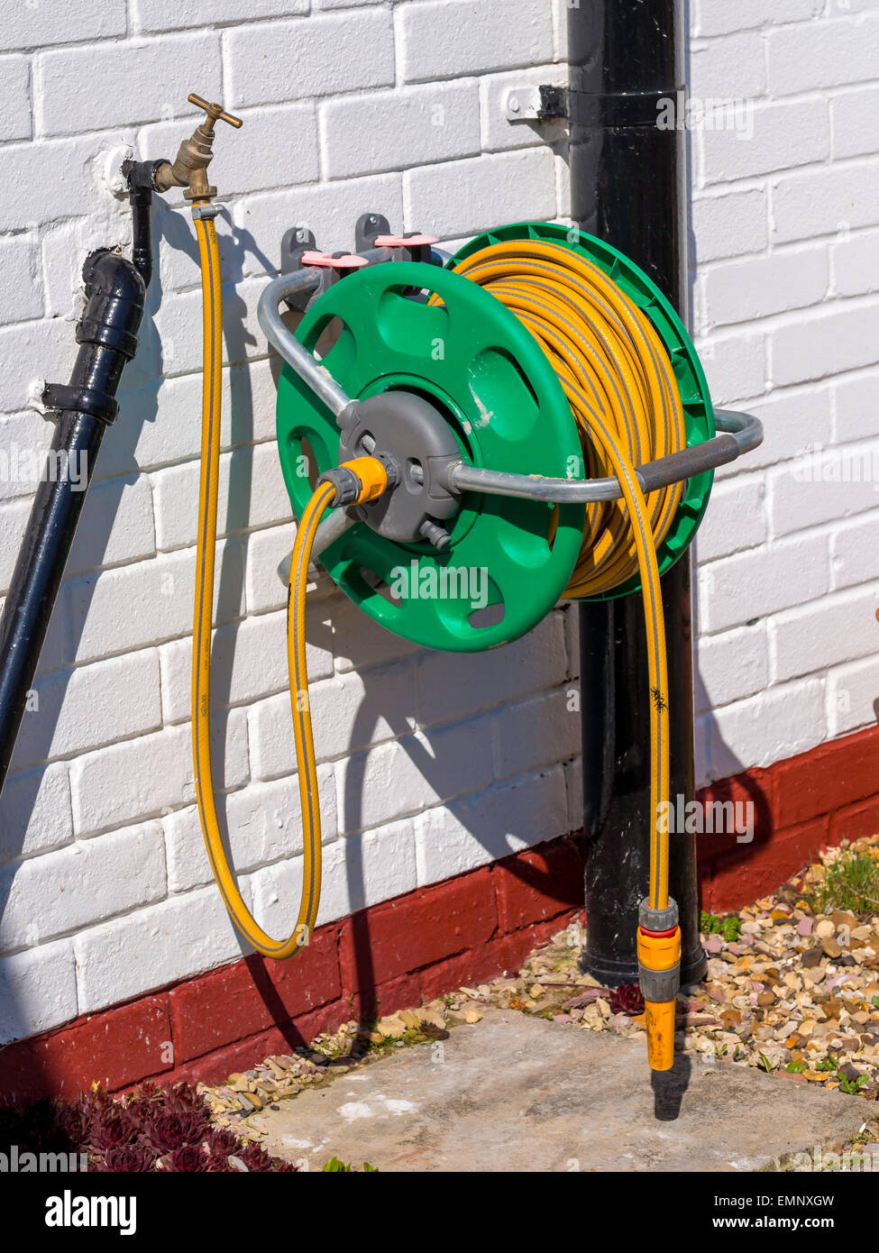 A Garden Hose Reel With Yellow Kink Resisting Hose Wall Mounted For  Convenient Deployment   Stock