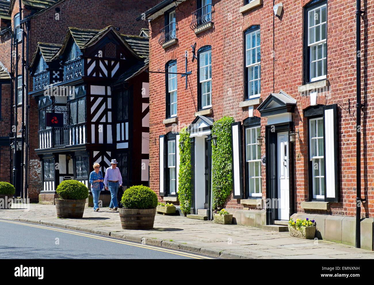 Couple walking down street in the village of Prestbury, Cheshire, England UK - Stock Image