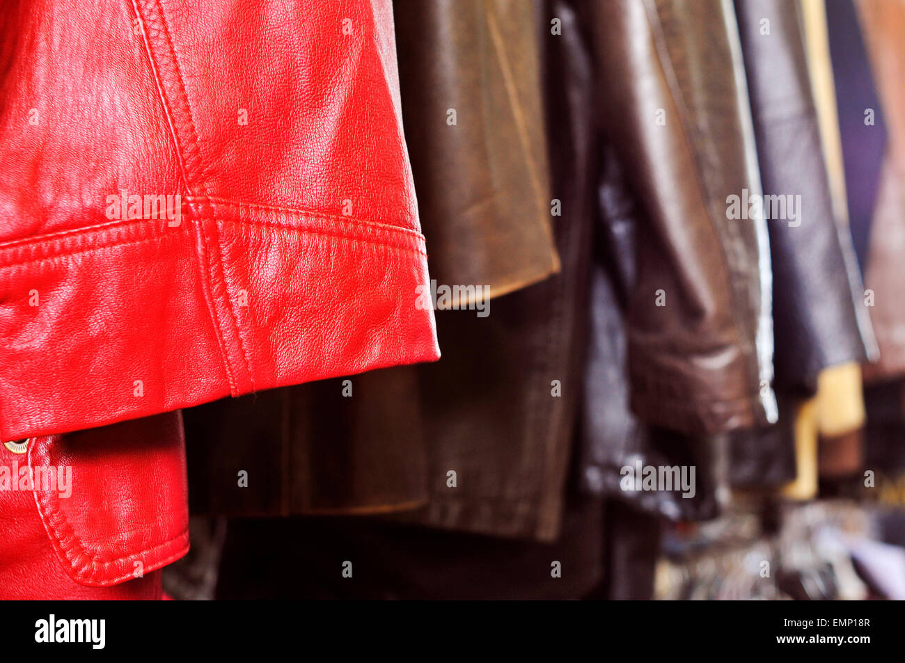 closeup of some used leather clothes, such as jackets and skirts, of different colors hanging on a rack in a flea - Stock Image