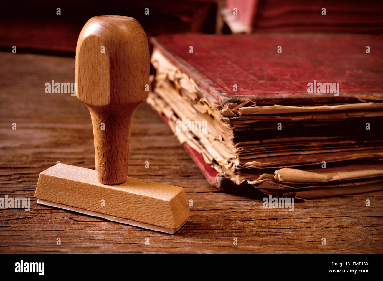 closeup of a rubber stamp and a worn-out old book, on a rustic wooden table - Stock Image