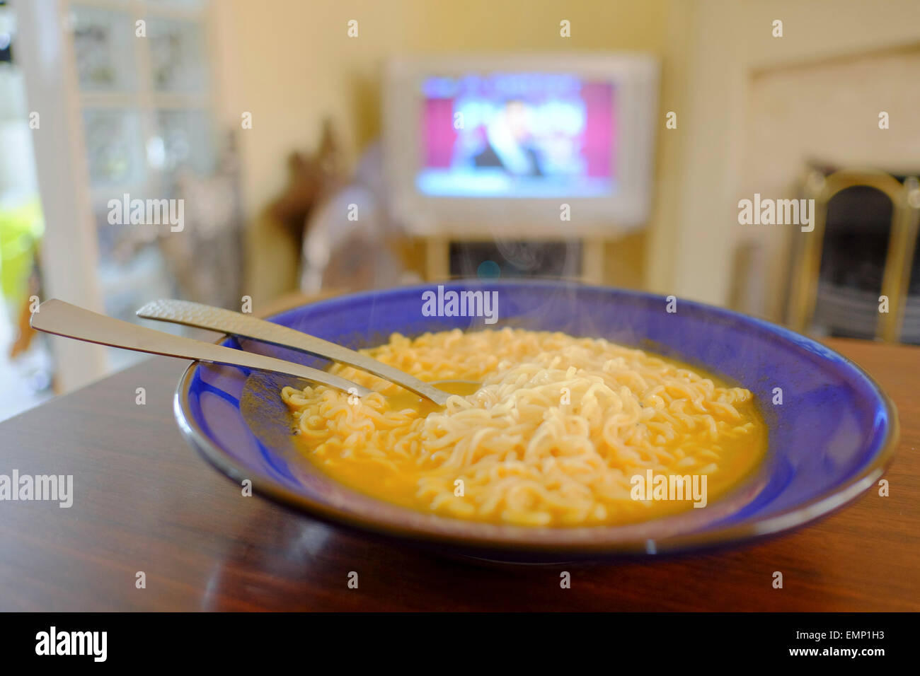 Eating noodles in front of television - Stock Image