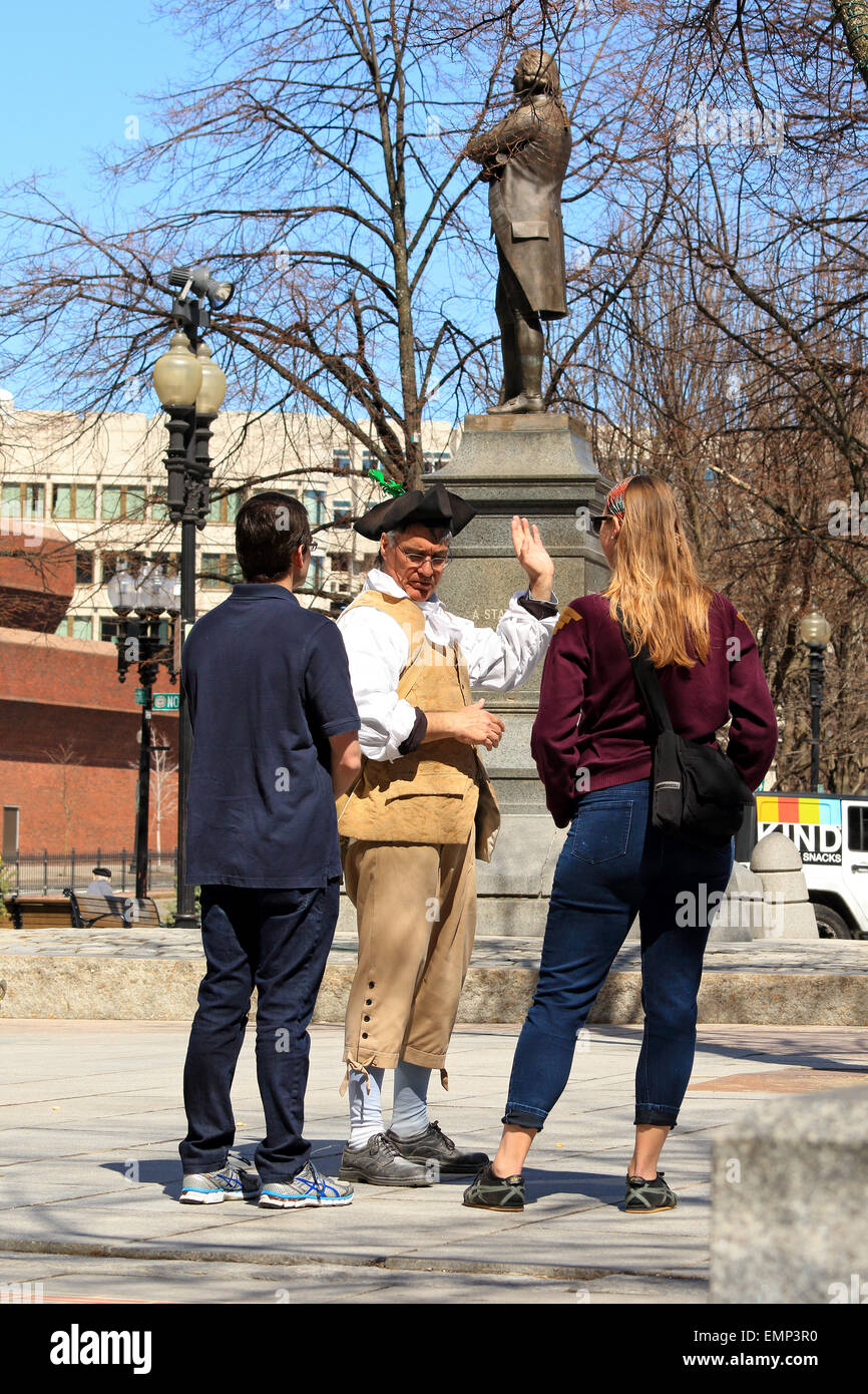 Boston Massachusetts Freedom Trail tour guide in period costume talks with tourists in near Sam, Samuel Adams statue - Stock Image