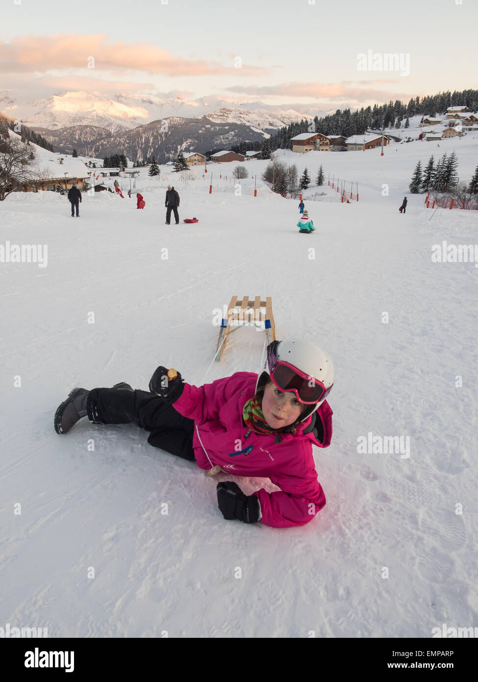 0cfb5adf2c5 small girl in ski clothes and helmet playing on the piste with a sledge  under evening