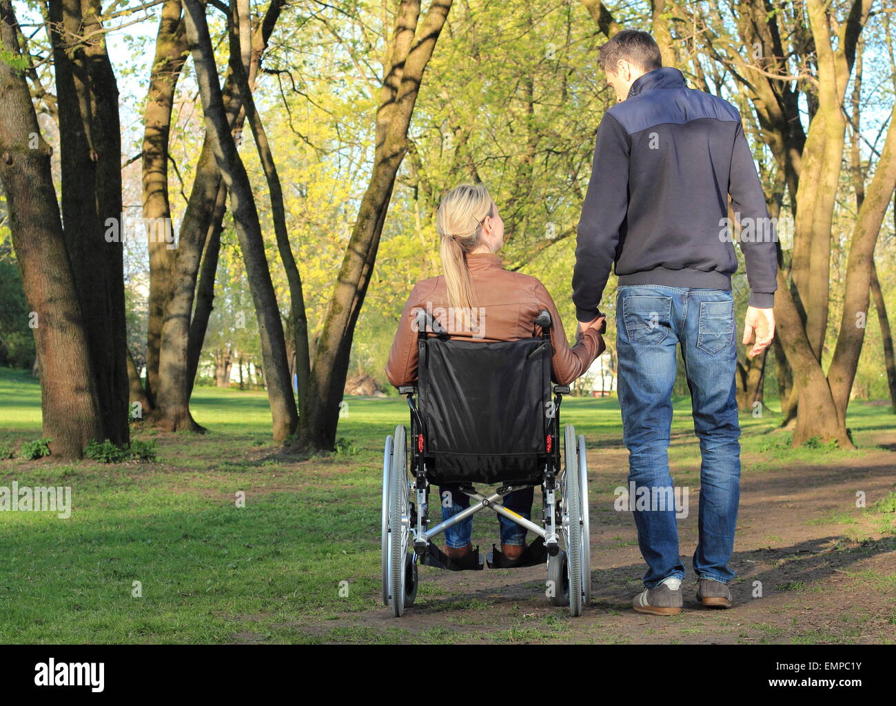 A Lovers couple in wheelchair and not handicapped - Stock Image