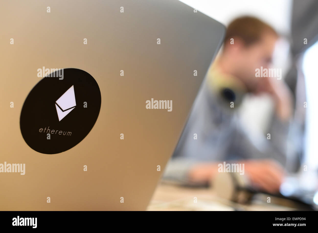 An Ethereum employee works behind a laptop with the Ethereum logo at the Ethereum DEV offices in Berlin, Germany, - Stock Image