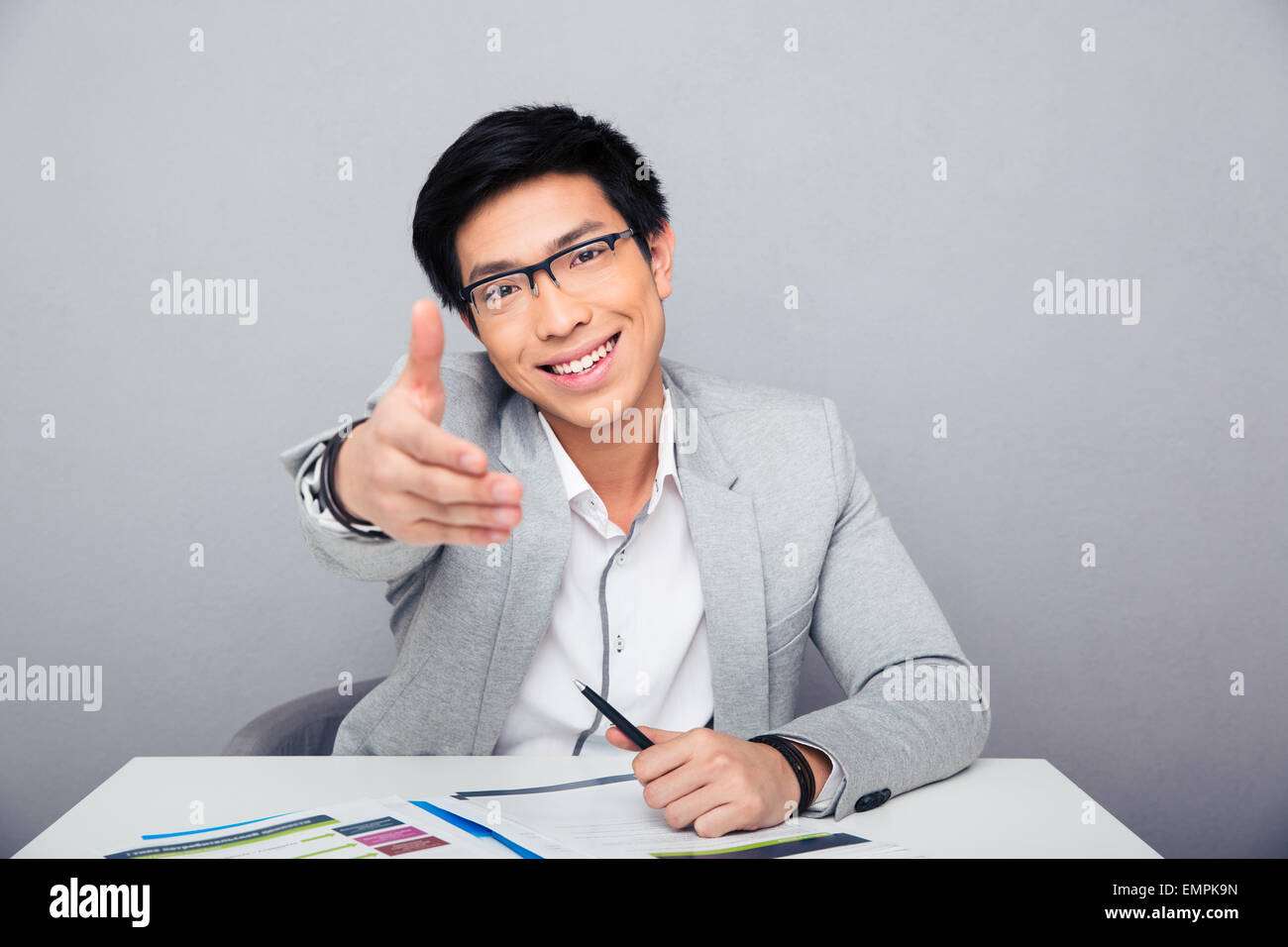 Happy young asian businessman sitting at the table stretching hand for handshake Stock Photo