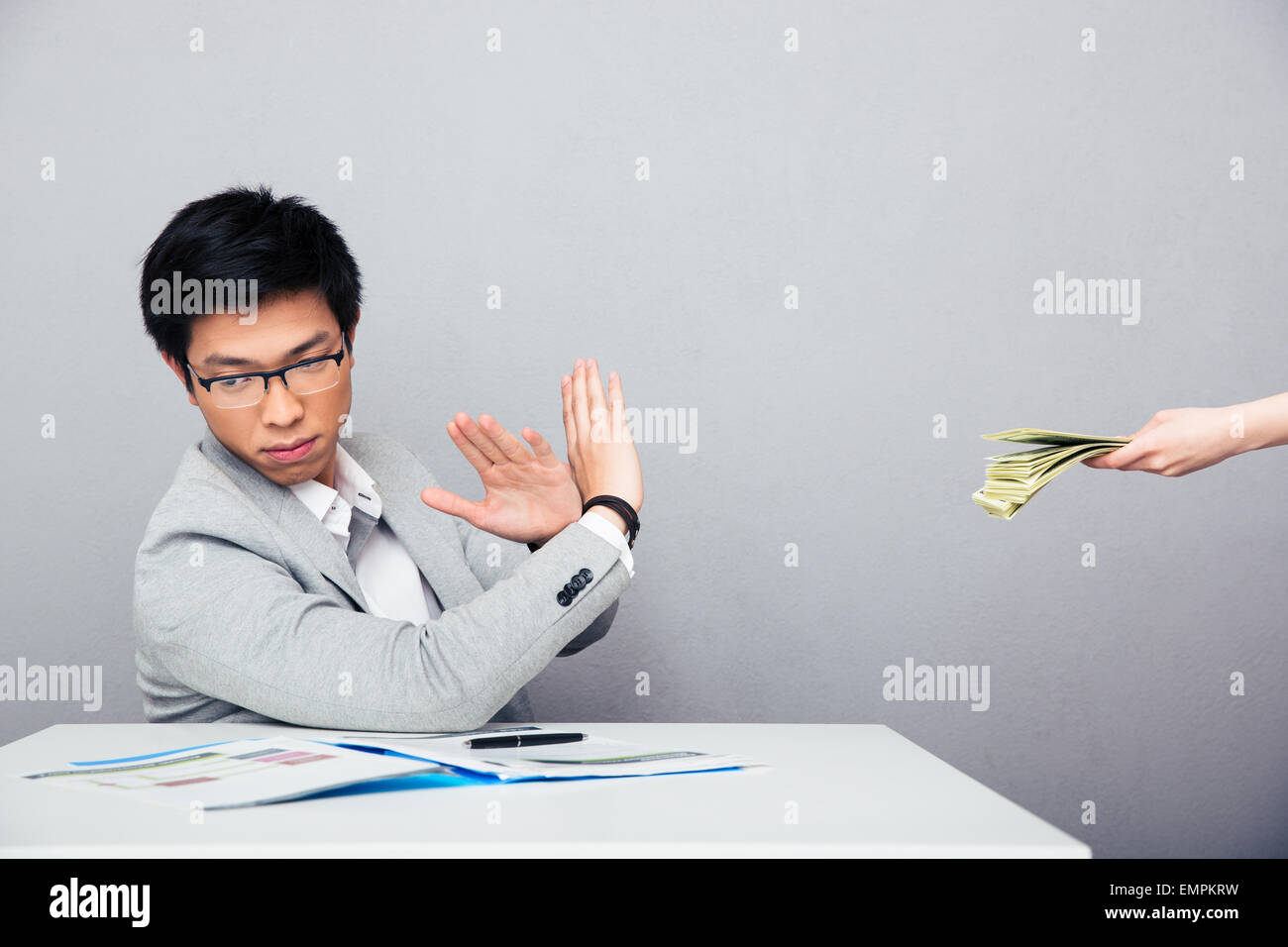 Asian young businessman gesturing stop sign while someone proposing money to him over gray background - Stock Image