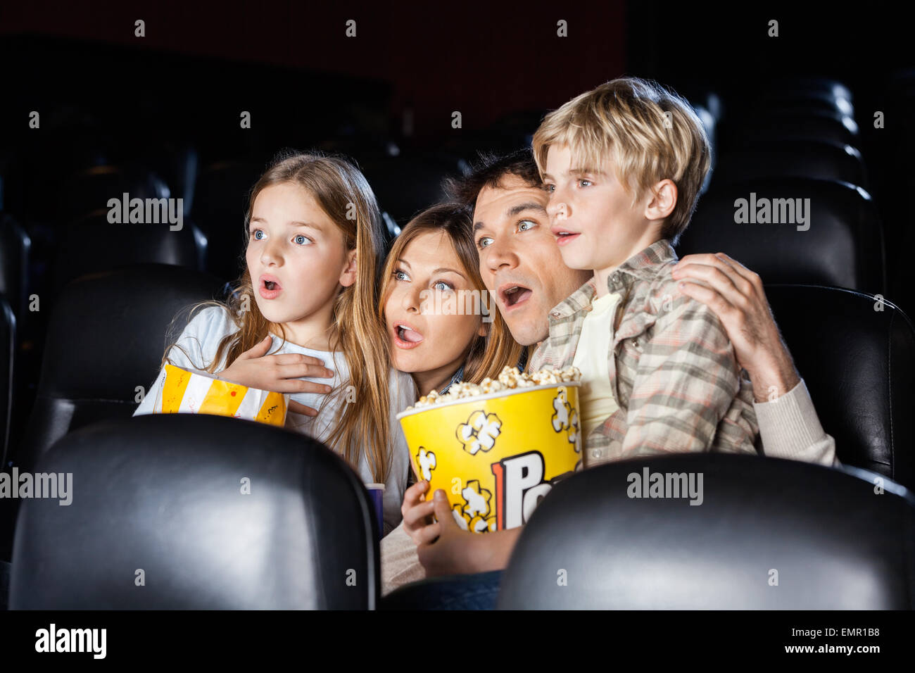 Shocked Family Watching Movie In Theater - Stock Image