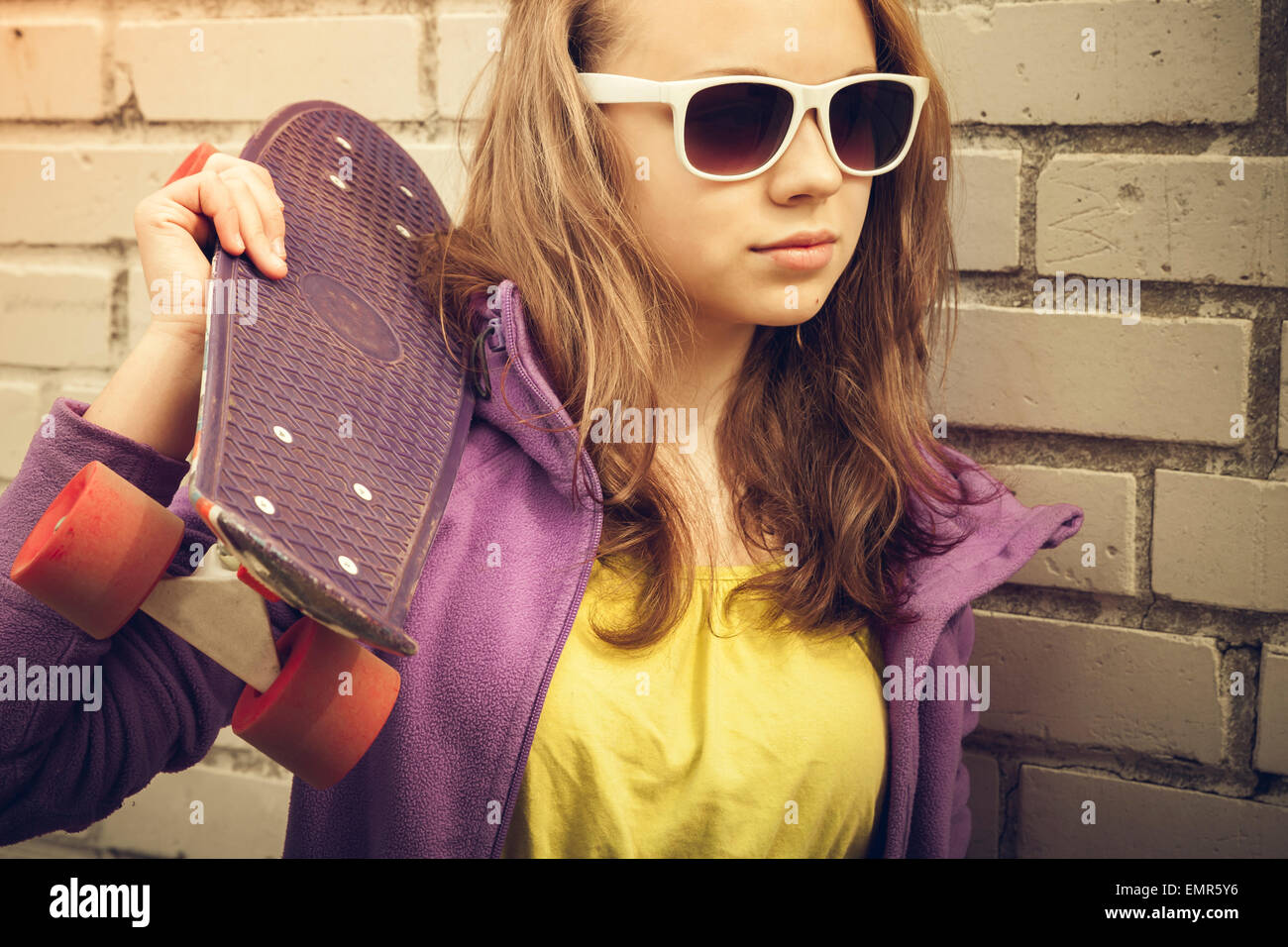 Of blond teen holding sunglasses