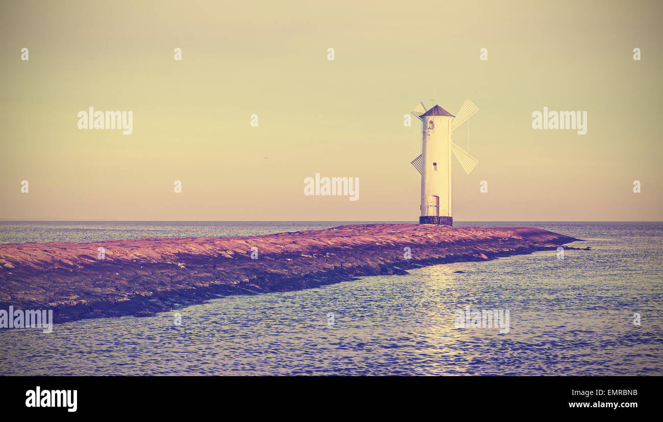 Retro vintage stylized sunrise over Baltic Sea coast, lighthouse in Swinoujscie, Poland. - Stock Image