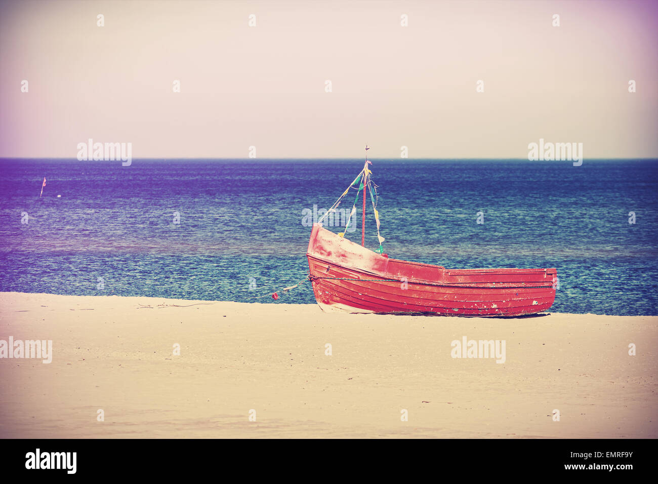 Vintage filtered photo of an old abandoned boat on the beach. - Stock Image