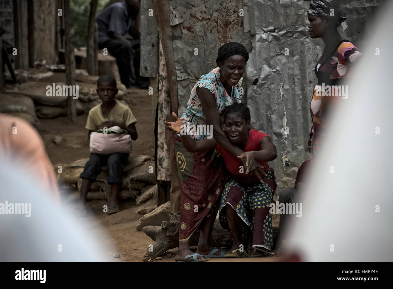 The wife of an Ebola victim breaks down after Liberian volunteer case investigation teams evacuated the Ebola victim - Stock Image