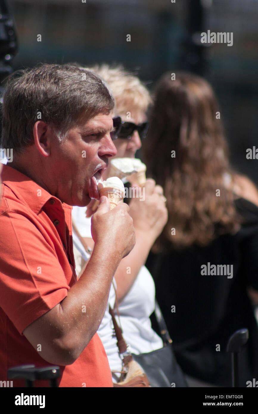 People eating ice cream in the sunshine, UK - Stock Image